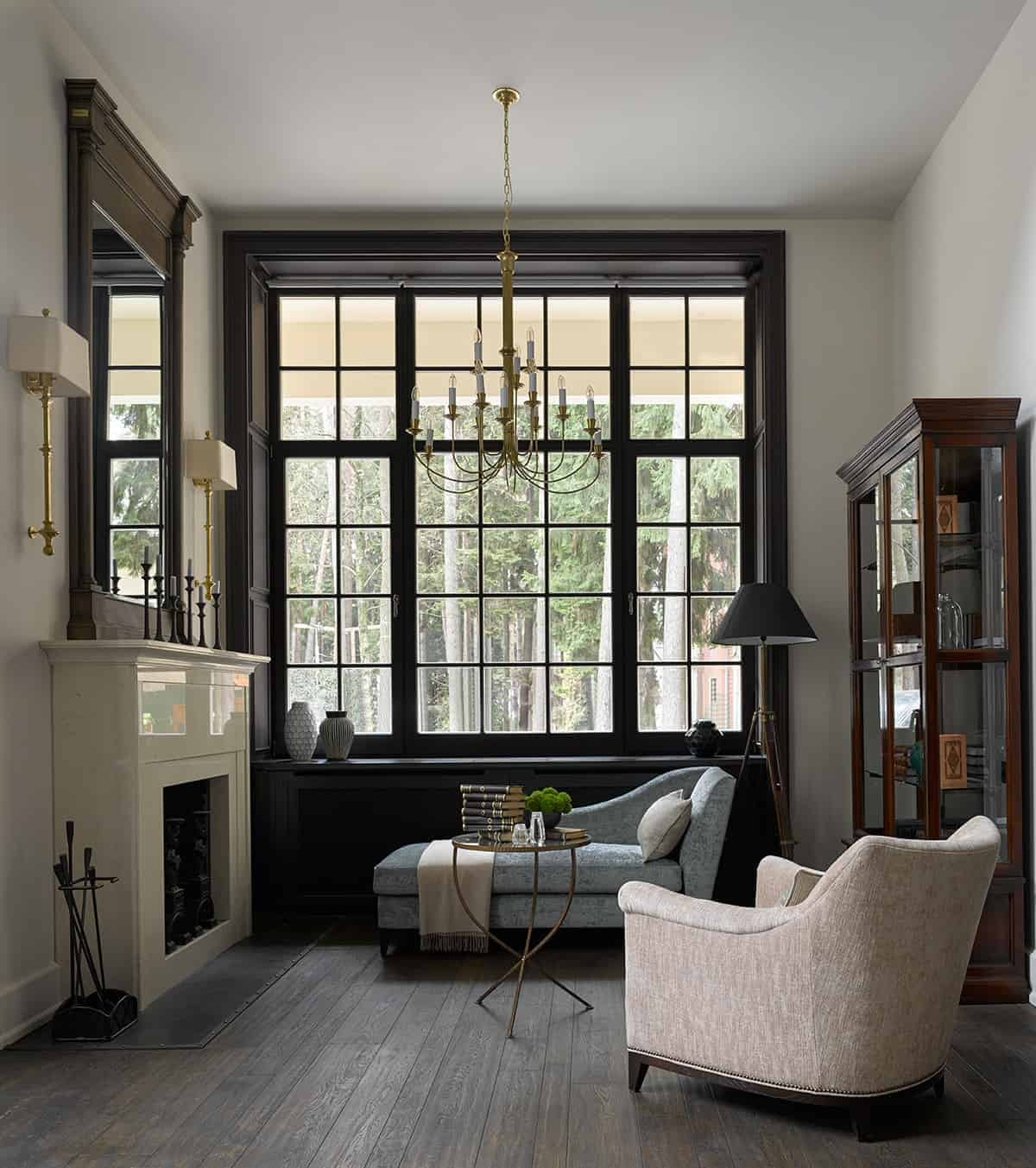 This is a small living room given the illusion of a bigger space thanks to its tall window that has a dark frame making the golden chandelier stand out.