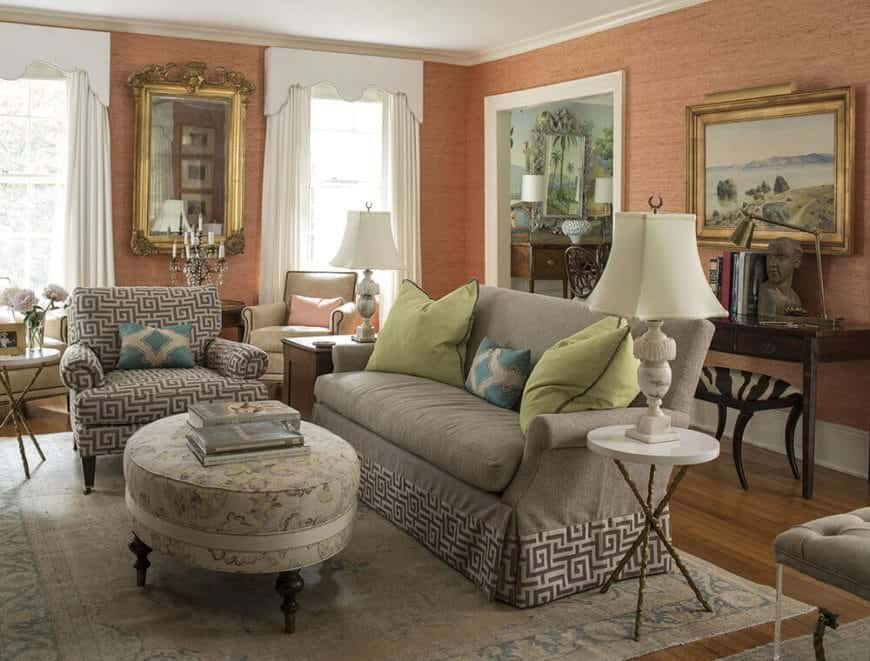 A delightful salmon pink hue is given to the walls of this living room that has a gray sofa and area rug complementing the white walls and curtained windows.