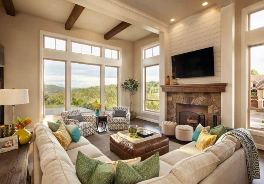 The spacious and grand aura of this living room is augmented by high beige walls and tall windows that reach the beige ceiling with exposed wooden beams matching the fireplace mantle and hardwood flooring.