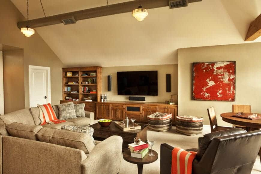 The beige walls and beige shed ceiling is adorned with exposed wooden beams that match the wooden structure below the TV that has built-in shelves and cabinets.