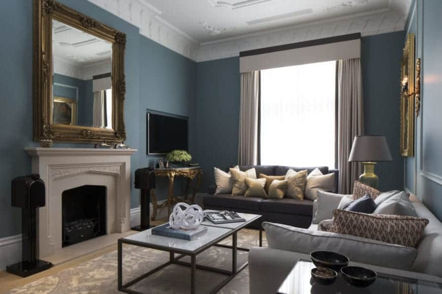 The simple white mantle of the fireplace stands out against the blue-green walls that has a wall-mounted mirror with an elegant frame. The sofas complement the walls.