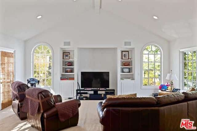 The white cathedral ceiling and white walls are accented with arched French windows that bring in natural light onto the brown leather couch set and beige carpeted flooring.