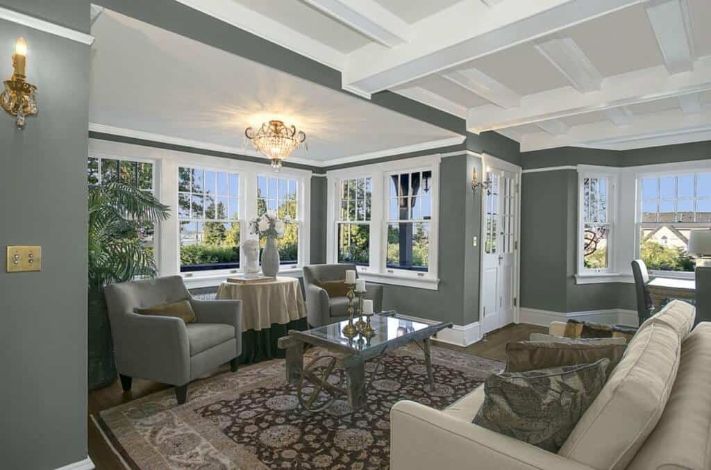 The white coffered ceiling is well contrasted by the dark gray walls that has an abundance of windows with white frames. These illuminate the hardwood flooring topped with a floral patterned area rug.