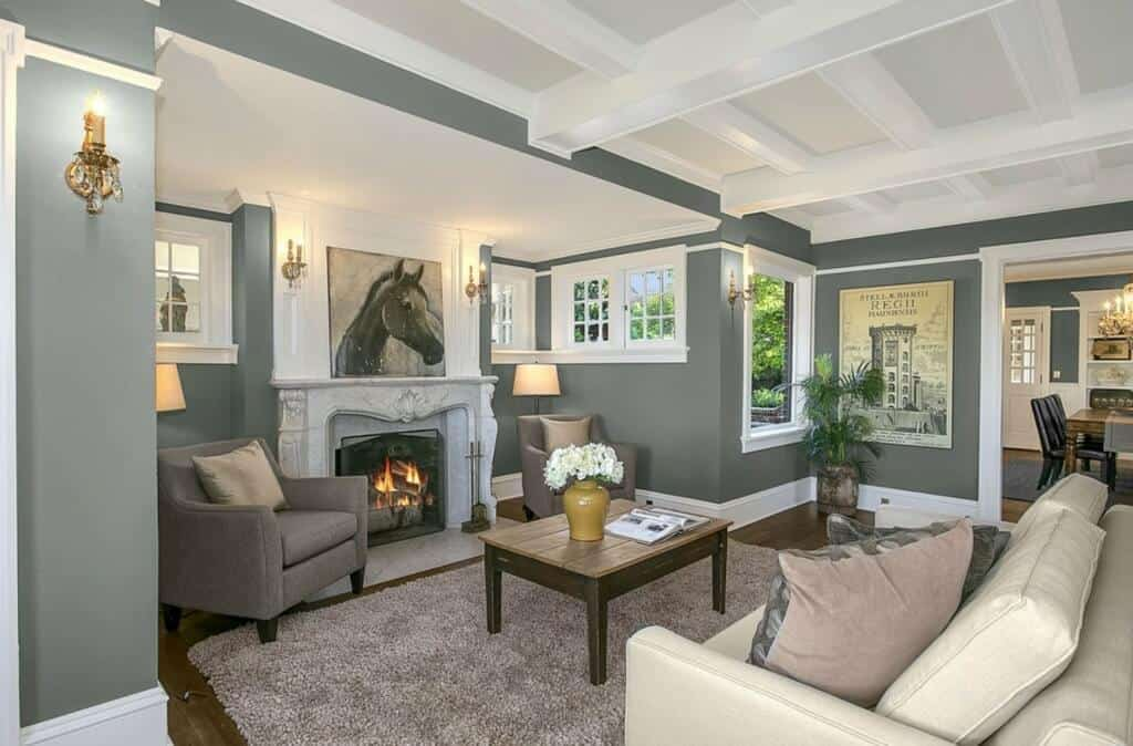 This living room highlights the artwork of a horse mounted over the white mantle of the fireplace flanked by two gray cushioned armchairs that blend with the gray walls.