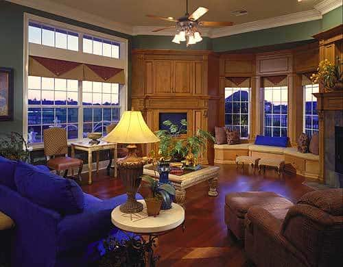 This is a spacious living room filled with charming contrasts like the green walls and the wooden structure that houses the TV, fireplace and even a window side sitting area for reading. The bright blue sofa contrasts the hardwood flooring and the wooden coffee table in the middle.