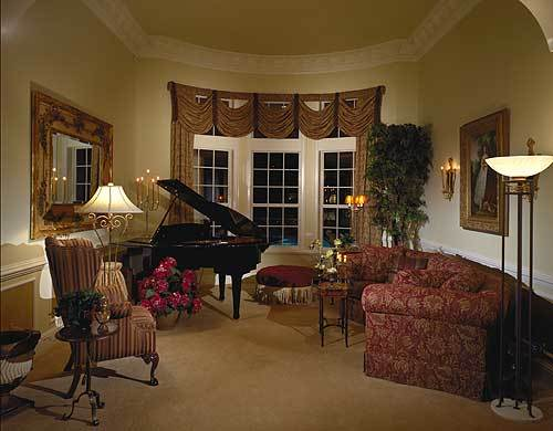 This is a classical formal living room with red floral curved sofa paired with beige carpeted flooring, beige walls and a beige ceiling. The black grand piano serves to complete the aesthetic.