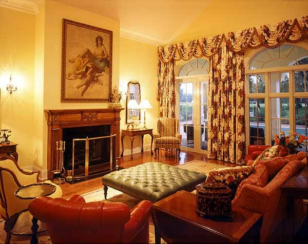 This warm and welcoming living room has floral curtains that frame the arched French glass doors and match the pillows on the sofa. This faces the fireplace with a wooden mantle and a wall-mounted classical painting above.