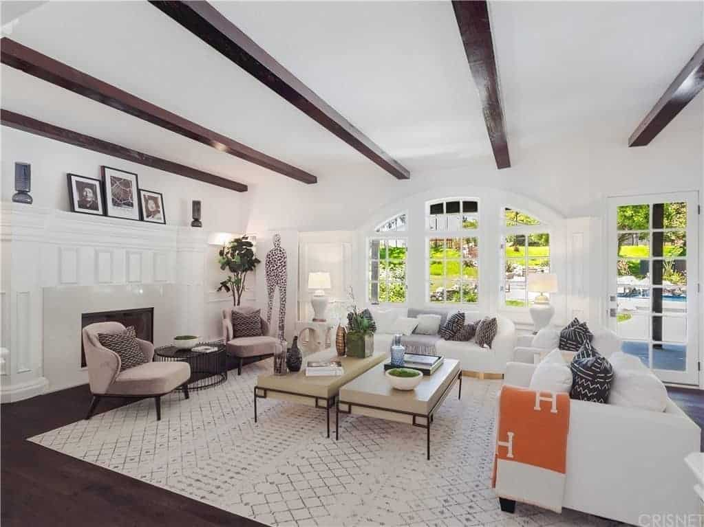 This bright and airy living room is predominantly white with hints of accent in the exposed wooden beams of the white ceiling that matches the hardwood flooring and the black and white photos propped on top of the fireplace's huge white mantle that matches the white sofas.