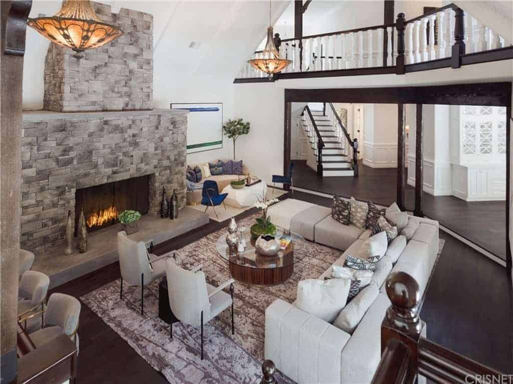 The L-shaped white sofa over the light gray area rug is facing the fireplace inlaid in a massive stone structure that reaches up to the high shed ceiling.