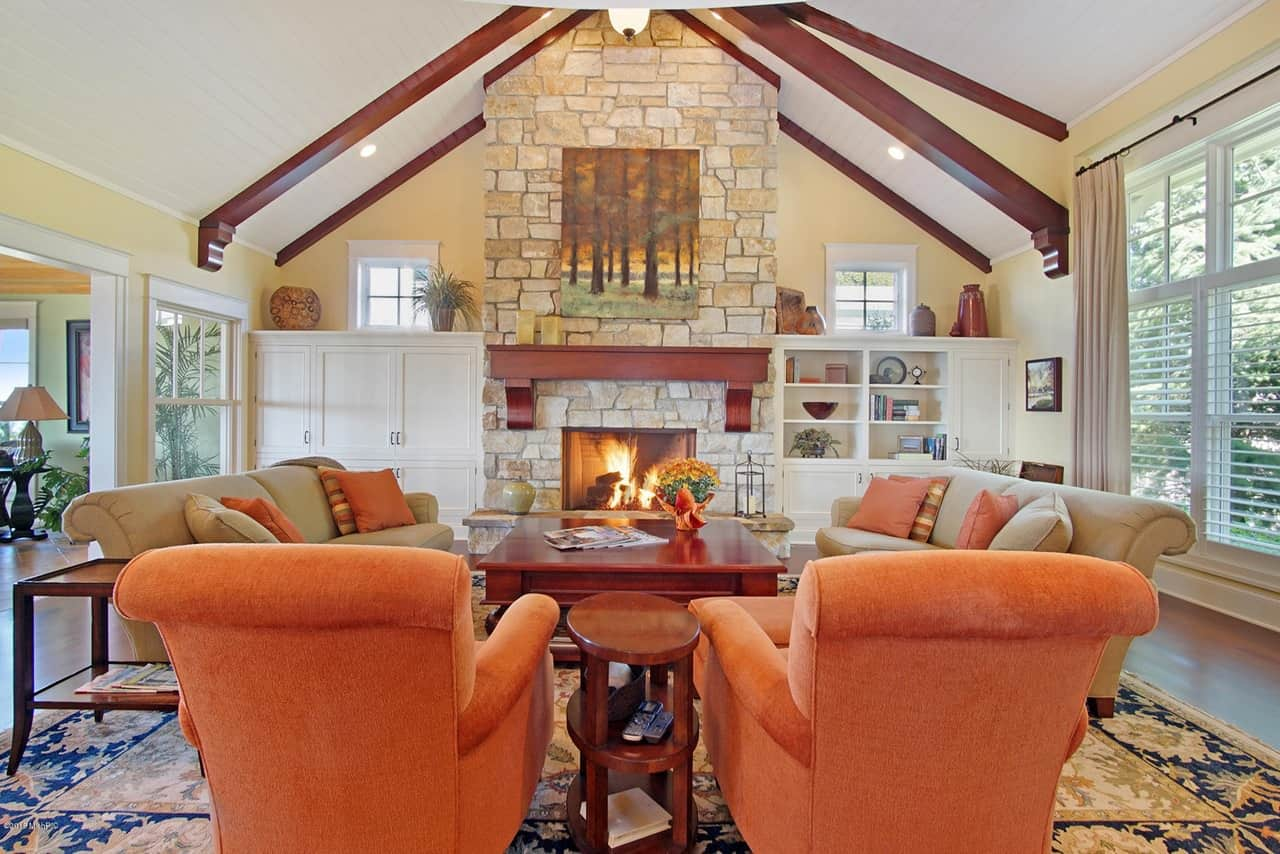 Large Living Room With Beamed Ceiling And Two Orange Armchairs Flanked Around A Fireplace