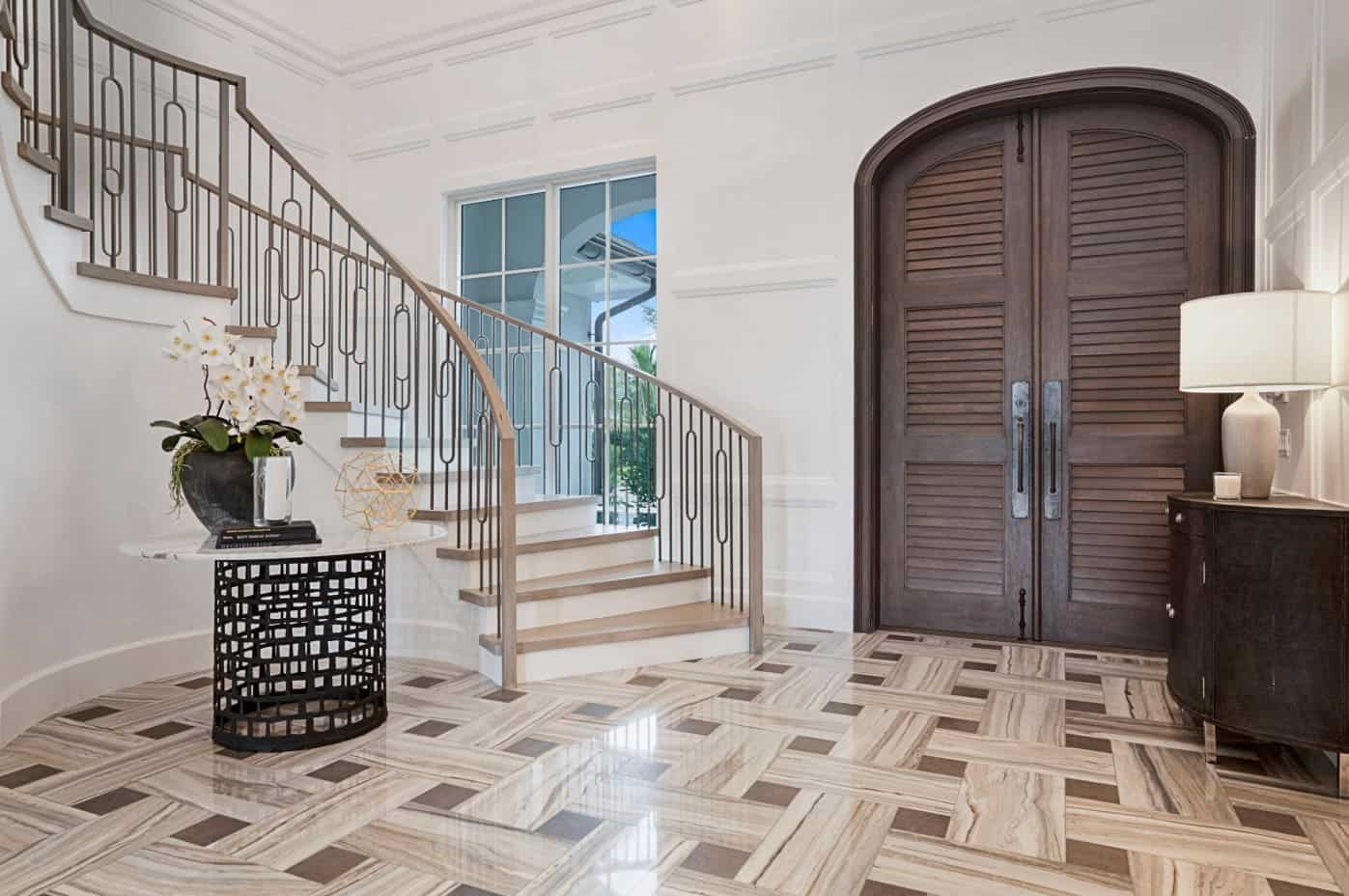 The brown patterned marble flooring of this Transitional-style foyer is perfectly matched with the wooden main doors as well as the drawers on the side bearing a table lamp across from the light brown and white staircase with simple wrought iron railings.