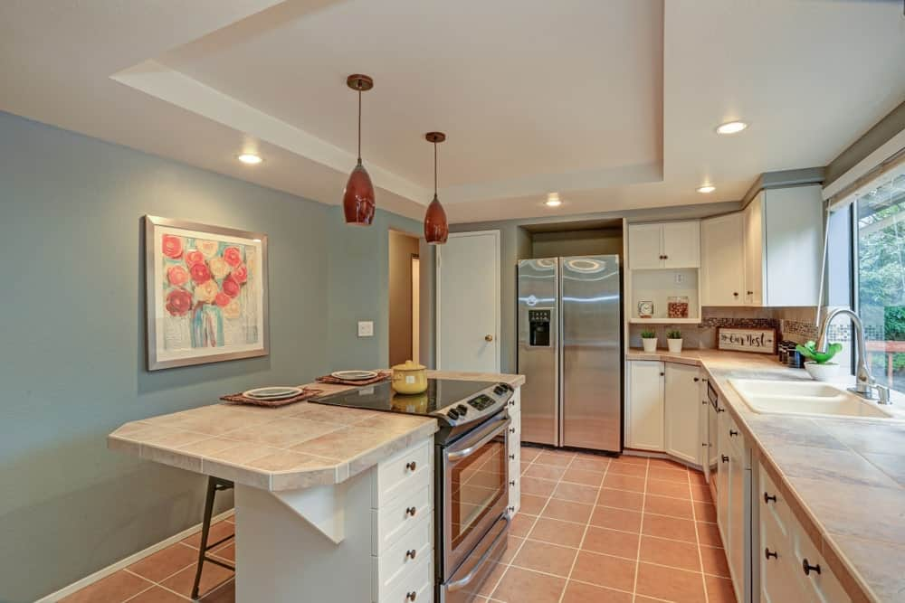 This kitchen features tiles flooring and tray ceiling with classy pendant lights lighting up the center island.