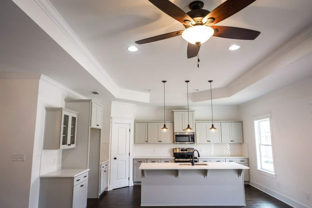 Pure white kitchen boasting a tray ceiling with pendant lights.