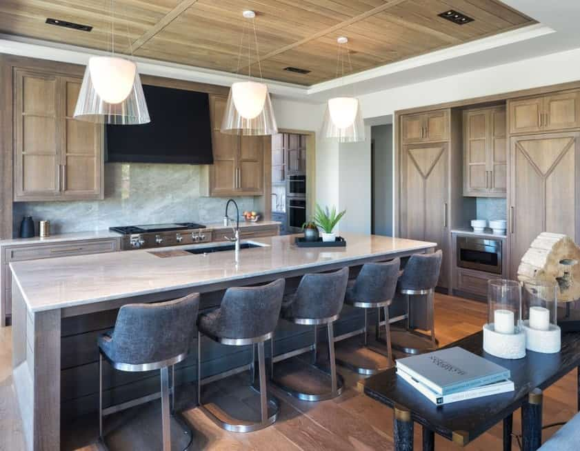 This kitchen offers a large center island providing space for a breakfast bar featuring cozy bar stools. The lighting looks so beautiful together with the tray ceiling.