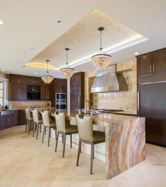 This kitchen boasts a very elegant tray ceiling boasting a set of glamorous pendant lights showering brightness down to the stunning center island.