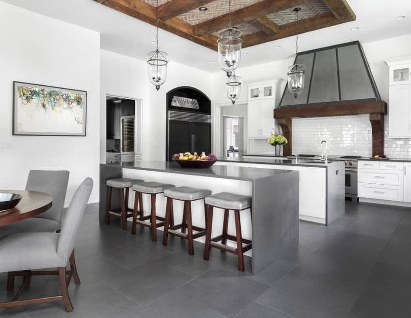 Large kitchen with gray tiles flooring matching the waterfall style breakfast bar lighted by glamorous pendant lights set on the tray ceiling.