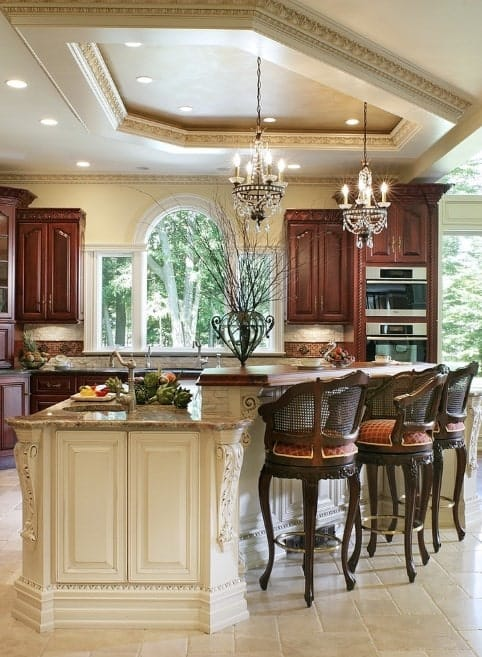 This kitchen boasts elegant small chandeliers set on the classy tray ceiling. The large center island provides space for a breakfast bar.