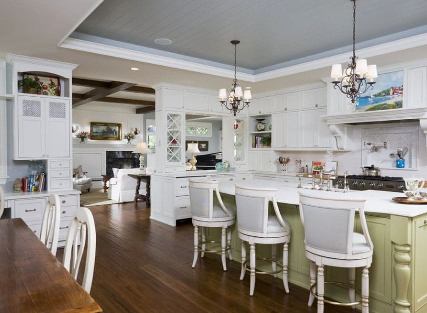 Large kitchen with hardwood floors and tray ceiling. There's a center island as well providing space for a breakfast bar lighted by a nice pair of pendant lights.