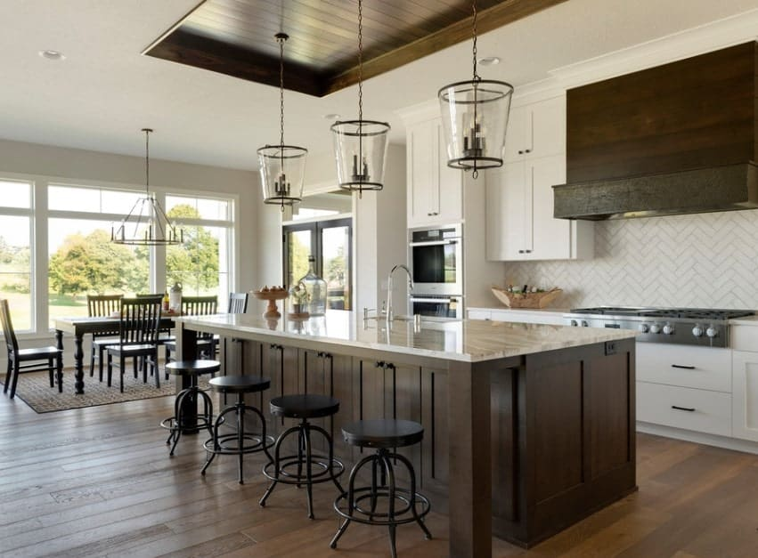 This kitchen features white walls and hardwood floors together with a large center island with marble countertop lighted by glamorous pendant lights set on the tray ceiling.