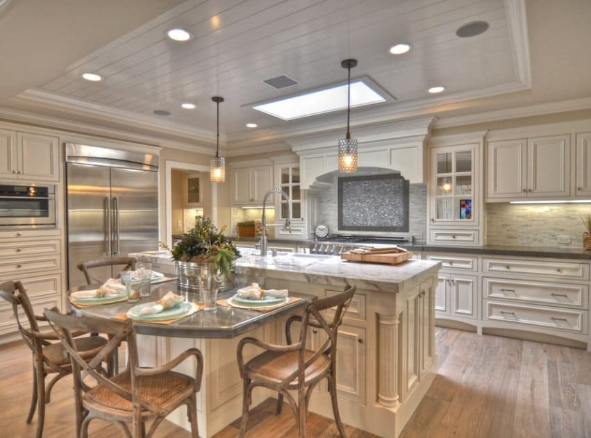 This kitchen boasts a combined center island with marble countertop and a dining nook set lighted by recessed and pendant lights on a tray ceiling.