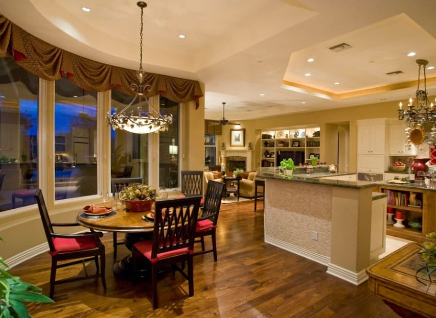 This kitchen offers a dining nook on the side lighted by a lovely pendant lighting. The tray ceiling above the main kitchen area looks very classy too.