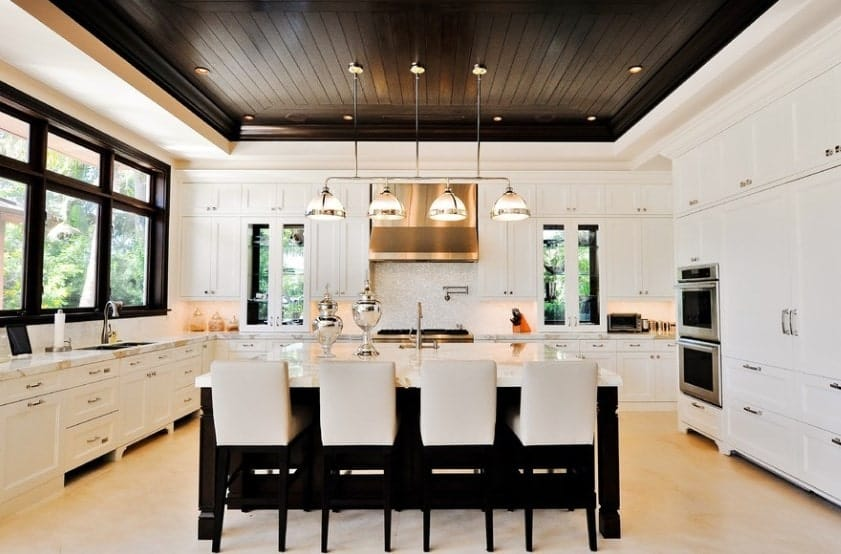 Large kitchen boasting white walls and black tray ceiling with pendant and recessed lights. The black shade around the kitchen area looks so elegant and stylish.