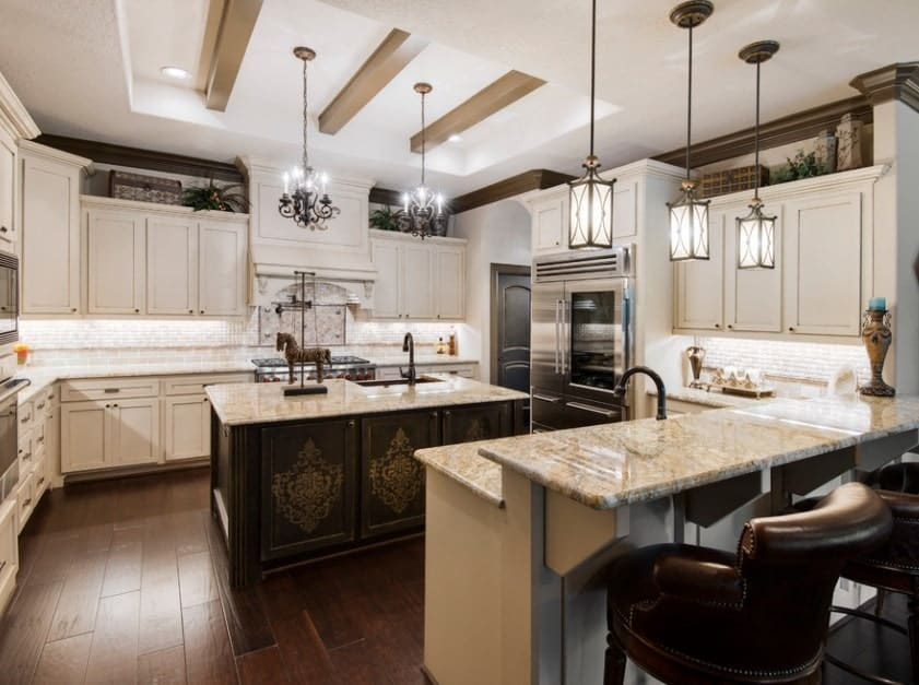This kitchen boasts elegant center island and breakfast bar, both featuring stunning marble countertops lighted by gorgeous pendant lights set on the tray ceiling.