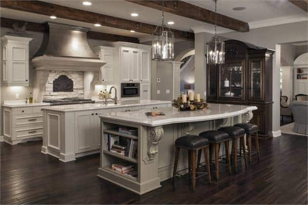 This gorgeous kitchen has a couple of kitchen islands that stand out against the dark hardwood flooring that matches with the exposed wooden beams of the ceiling that hangs pendant lights over the breakfast bar.