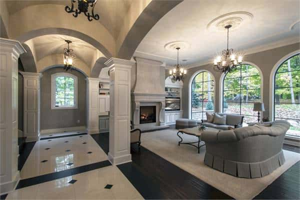 This spacious living room is festooned with elegant arches and pillars as well as chandeliers that hang over the gray sofa set on the light area rug of the dark hardwood flooring. These are then warmed by the large fireplace on the far side.