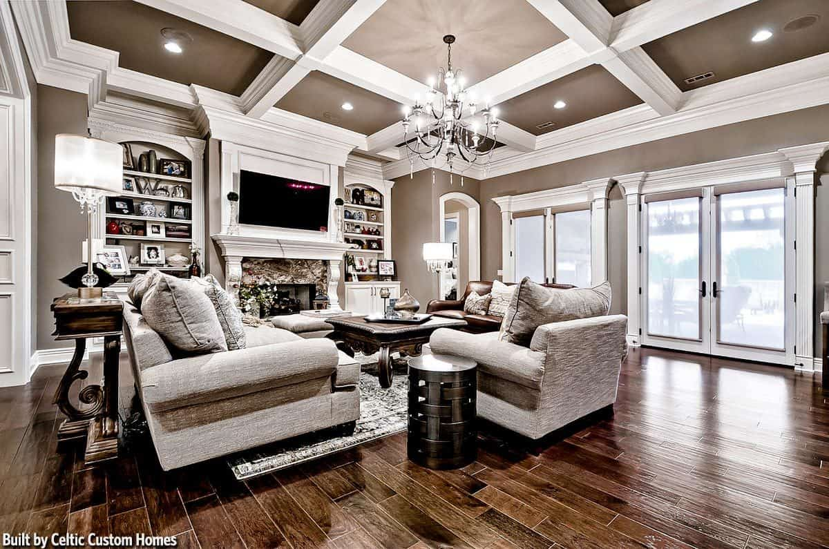 This is a spacious living room with hardwood flooring to complement the coffered ceiling and its bright crystal chandelier. This hangs over the wooden coffee table surrounded by sofas across from the fireplace.