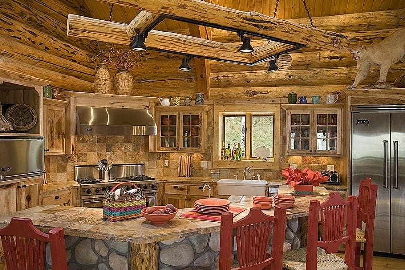 This rustic and charming kitchen has a large curved stone kitchen island with a stone countertop for its breakfast bar paired with red wooden stools. This kitchen island is then topped with a hanging wooden structure that houses modern lighting.