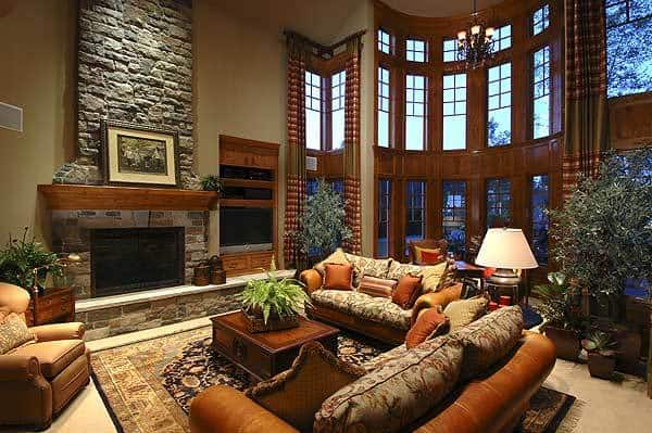 This is a large living room with a tall ceiling paired with a tall textured stone fireplace with a wooden mantle. Across from this is a couple of brown leather sofas paired with a small wooden coffee table in the middle of the patterned area rug.