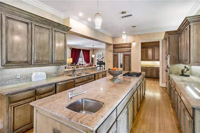 This kitchen has a beautiful elongated kitchen island with the same cabinetry as those lining the walls. These are then complemented by a hardwood flooring and white ceiling that hangs pendant lights over the island that houses the cooking area on one end and the sink on the other.