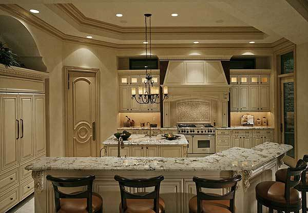 The gorgeous kitchen has matching cream-colored cabinetry to blend with the tray ceiling that hangs a small chandelier over one of the two kitchen islands.