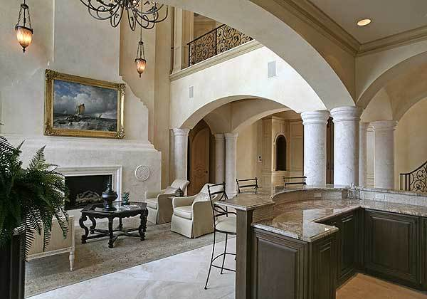 This living room has a tall ceiling that hangs a wrought iron chandelier to match the railings of the indoor balcony as well as the dark coffee table across from the large fireplace topped by a beautiful painting.