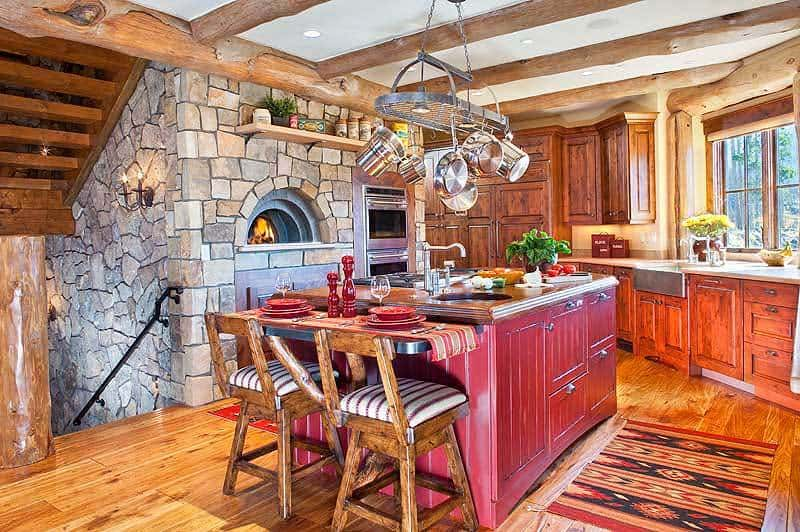 This is a warm and cozy kitchen dominated by a large stone structure housing the wood-burning oven across from the red wooden kitchen island topped with a hanging pot rack from the beige ceiling with exposed wooden log beams that match the hardwood flooring.