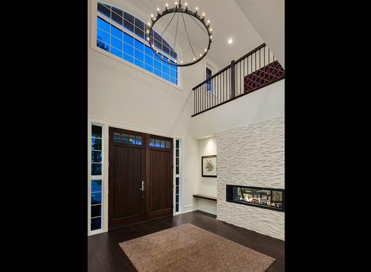 This lovely foyer has large wooden double doors that match well with the dark hardwood flooring topped with an area rug and a round chandelier from the tall ceiling. These are then warmed by the modern fireplace on the side.