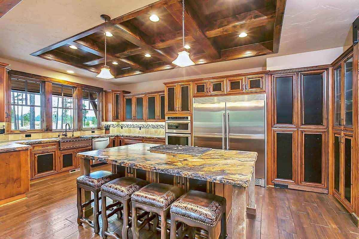 The elegant dark wooden coffered ceiling of this kitchen matches perfectly with the surrounding wooden cabinetry and the hardwood flooring with a wooden kitchen island in the middle topped with an earthy marble slab countertop.