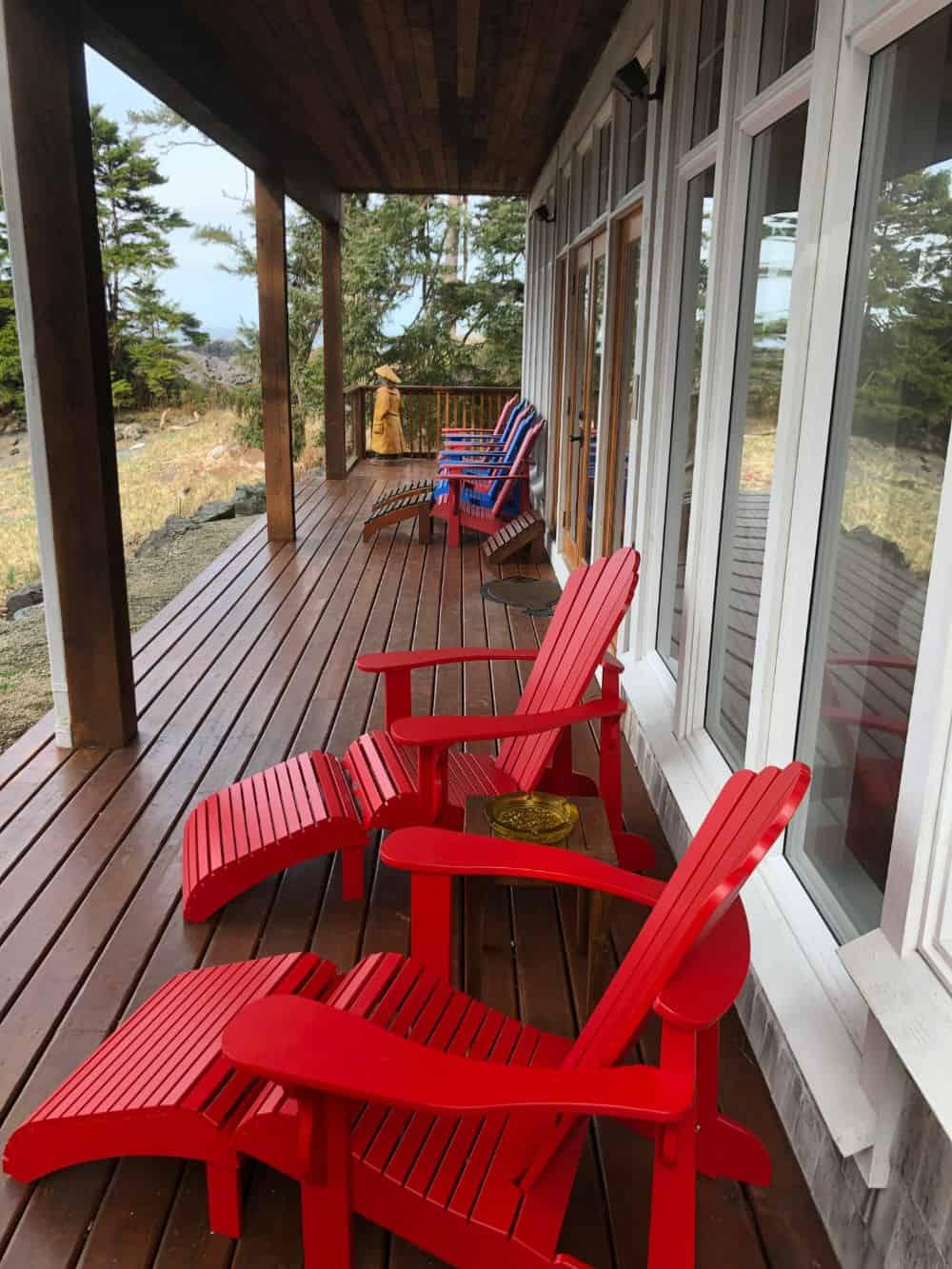 The veranda-style deck runs along the entire width of the home and is furnished with several comfortable chairs.