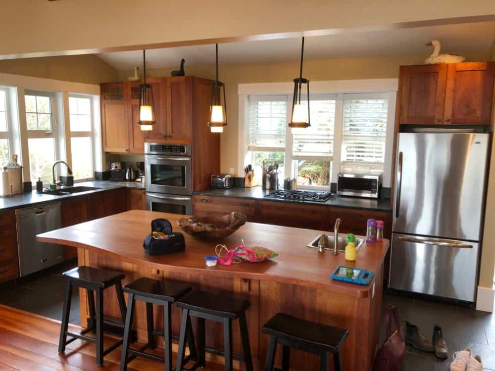 The kitchen is large in L-shape layout with wood-surface island.