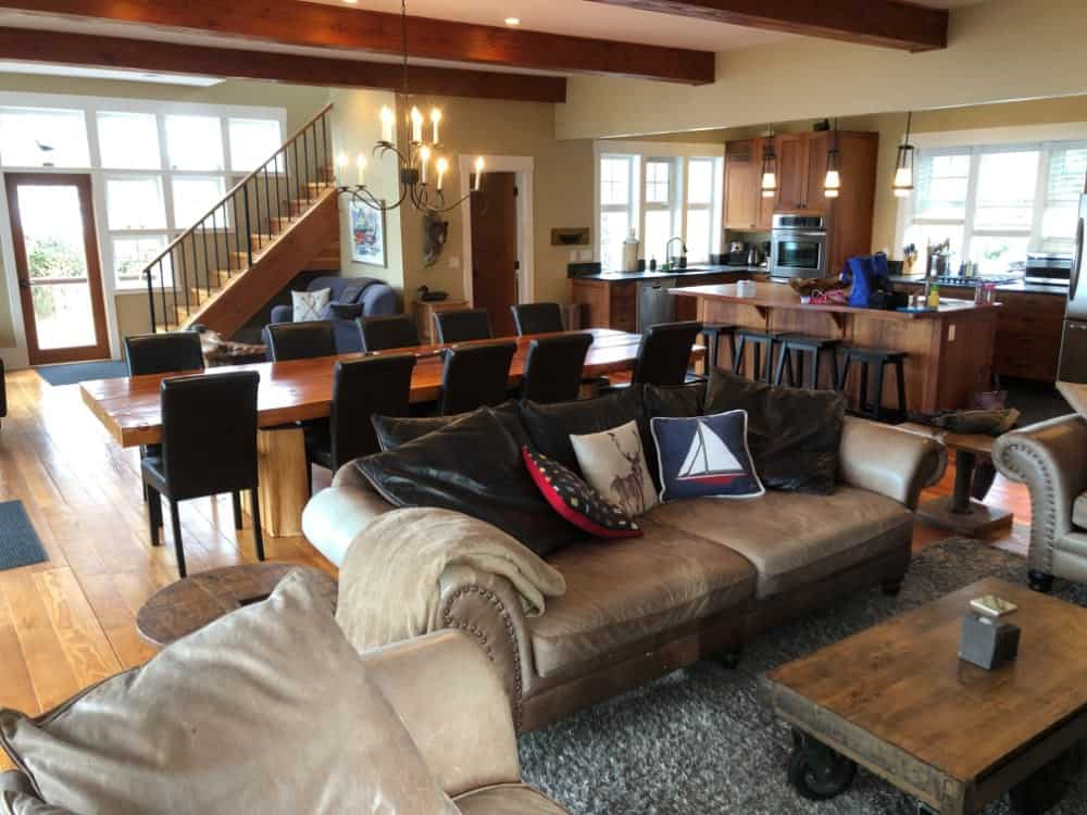 Black Rock beach house in Ucluelet - the great room viewed from the living room with huge dining table, l-shaped kitchen and reading area.