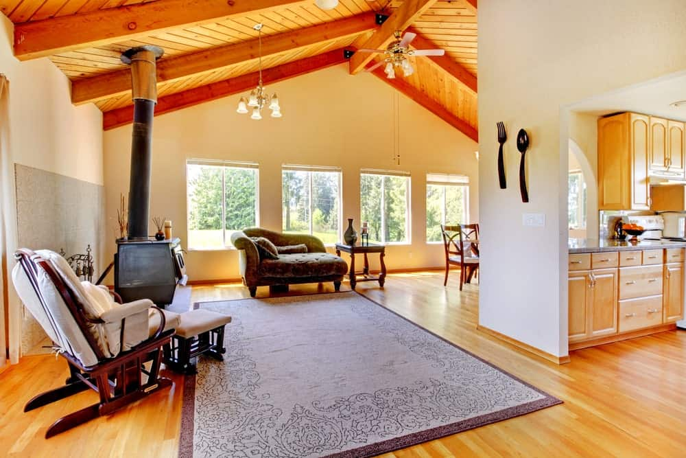 The vaulted ceiling lighted by gorgeous lights turns this space into an exquisite place with nice seats and a fireplace.