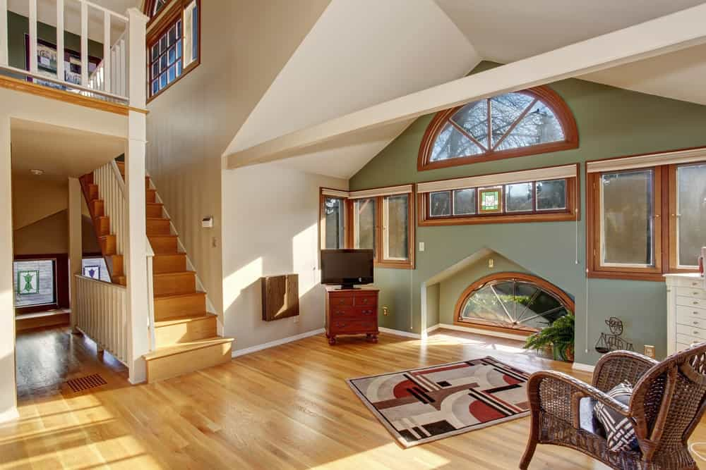 This spacious home features hardwood flooring and white and green walls along with a vaulted ceiling.