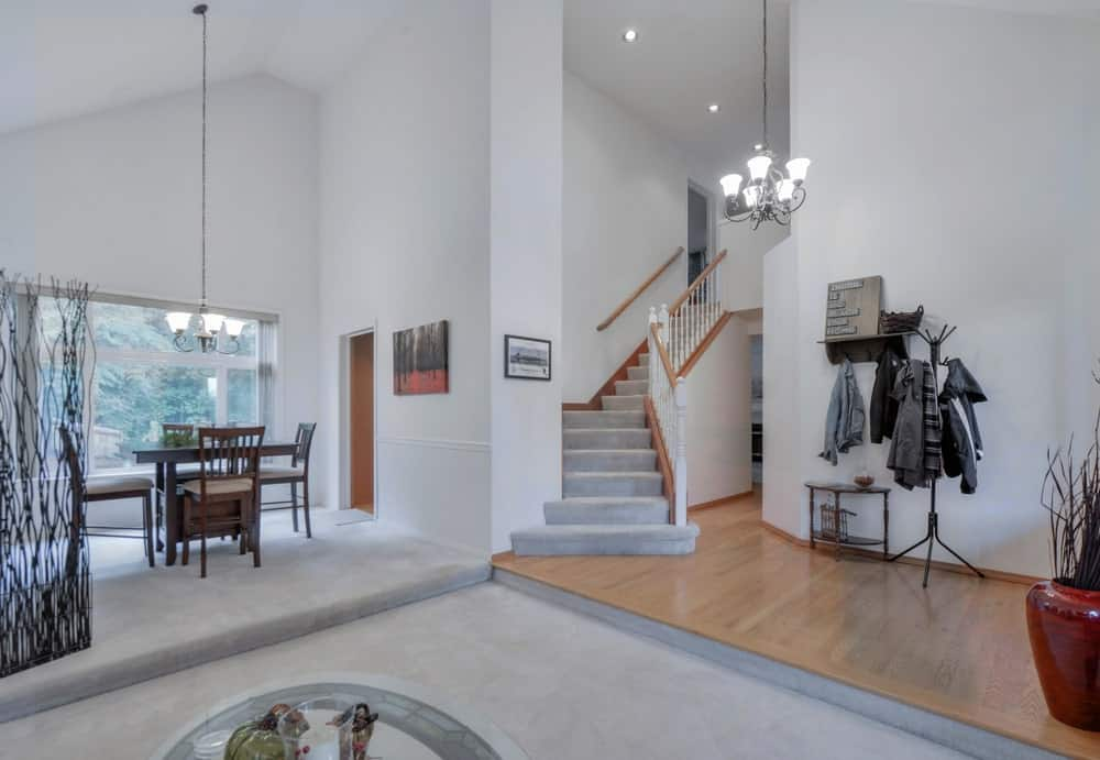 This home boasts white walls and carpet flooring along with a vaulted ceiling lighted by small and classy chandeliers.