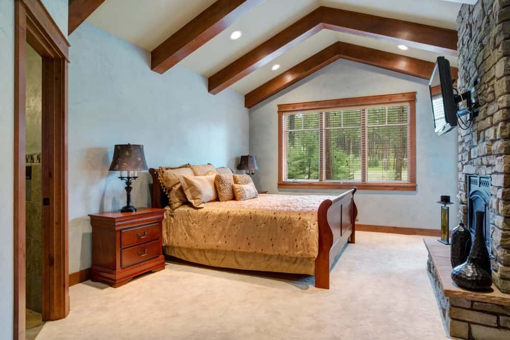 This bedroom features white carpet flooring and a vaulted ceiling with exposed beams. There's also a stylish fireplace.