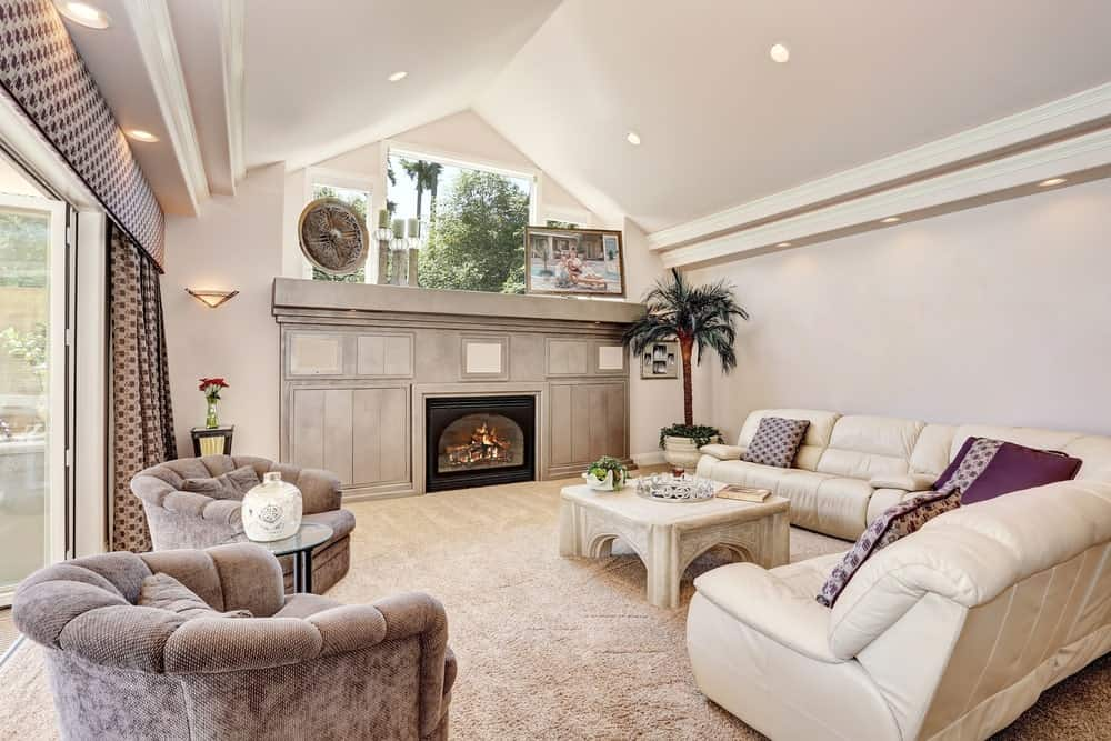 White formal living room boasting classy carpet flooring and white cozy sofa set along with a fireplace.
