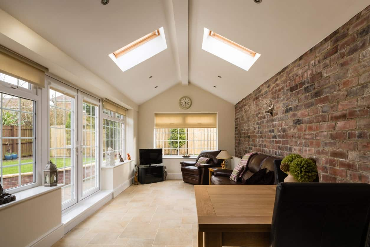 A stylish formal living room featuring a brick wall and a vaulted ceiling offering skylights.