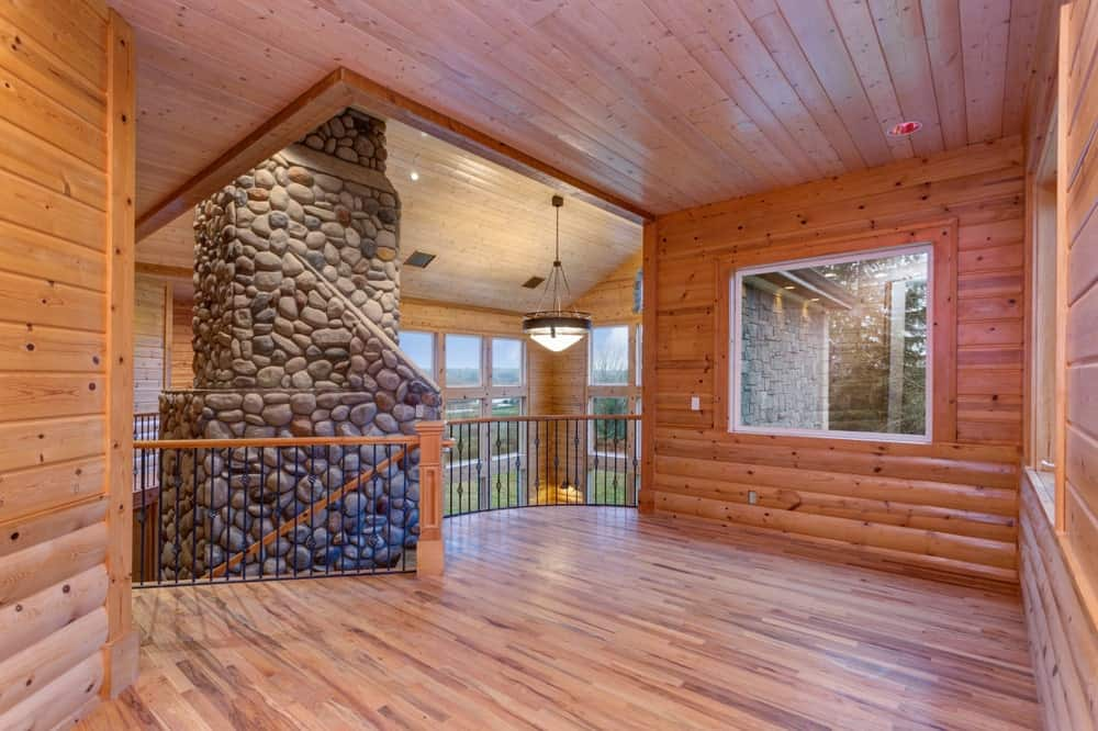 A stunning home covered in wooden walls, floors and ceiling along with a pillar made of stones.