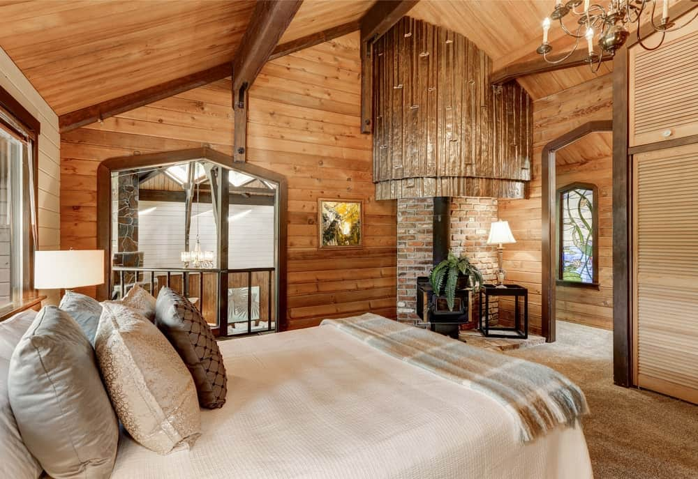 A stunning master bedroom surrounded by wooden walls and ceiling and is lighted by a glamorous chandelier.
