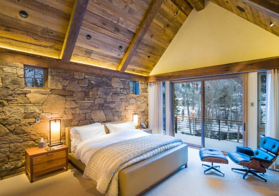 A rustic bed with a stone wall and a vaulted ceiling along with carpet flooring and warm white table lamps.